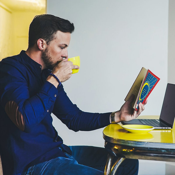Man reading a book and sipping lion's mane & reishi coffee from a yellow cup.